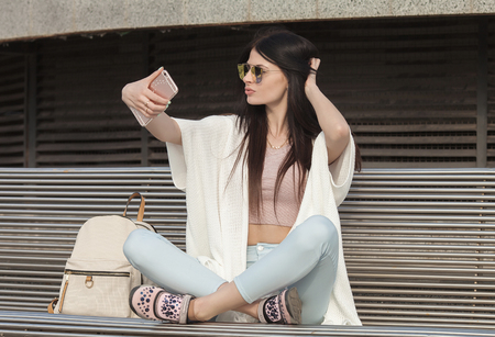 hands free phone: young brunette woman making self portrait using smartphone. girl making selfie. woman in park. Focus on woman. Blurred background.
