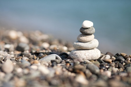 Pyramid of stones on the beach. Blurred background. Stock Photo
