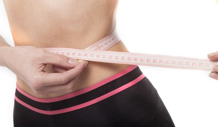 centimeters: Fit and healthy young lady measuring her waist with a tape measure in centimeters and millimeters Stock Photo