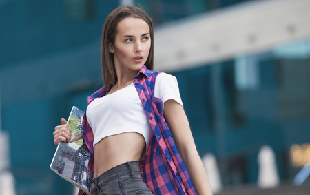fashion magazine: Beautiful brunette young woman wearing black jeans, white shirt and walking on the street . Fashion magazine in hand. Blurred background. Stock Photo