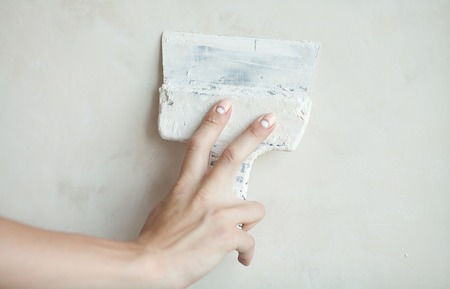 putty knives: Woman hand with manicure. Closeup of palette-knife or scraper and cement filling for house renovation construction. Stock Photo