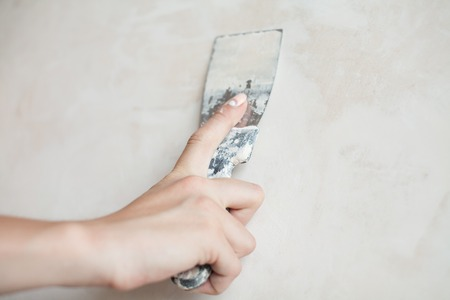 Woman hand with manicure. Closeup of palette-knife or scraper and cement filling for house renovation construction. Stock Photo
