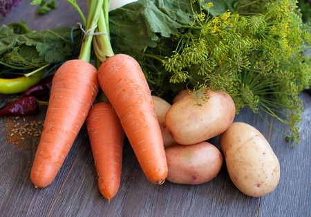 young potatoes and carrots on wooden background