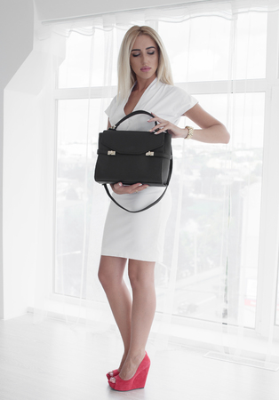 doctor money: portrait of blonde business woman. Wearing white elegant suit and taking working bag in the hand