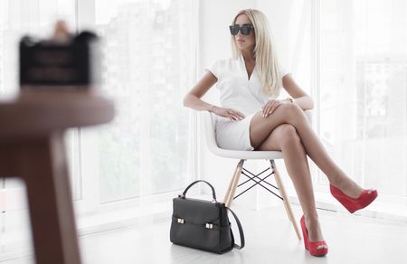 Young business woman in sunglasses wearing white and red shoes sitting on chair. Black handbag near sexy lady.