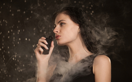 Young beautiful woman vaping e-cigarette. Water flowing on woman face. Stock Photo
