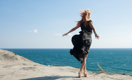 Girl in black dress billowing out flying transparent fabric. Model on a mountian and sea background holding a flying dress