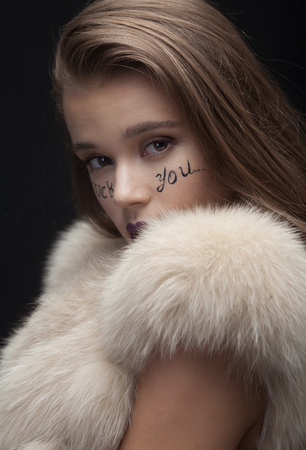 foda: Beauty Fashion Model Girl in Blue Mink Fur Coat. Beautiful Luxury Winter Woman with creative make writing fuck you on face