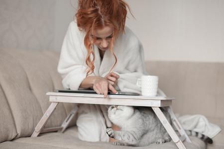 Lady playing with cat in bed. Wearing casual white attire.