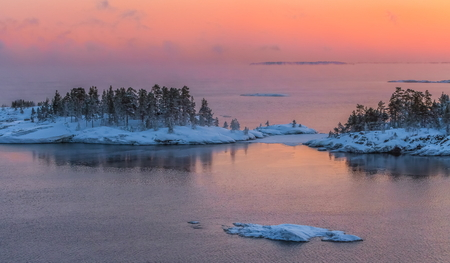 A colorful sunset on the Ladoga lake in the frost. Winter day. Open water hovers from frost. Islands in the snow. Stock Photo