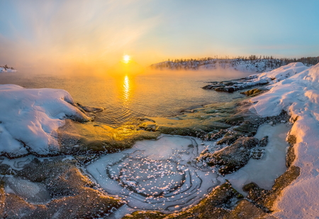 Winter dawn in the bay on the lake. Lake Ladoga in the cold. Open water hovers from frost. Granite skerries in the snow, in the ice.