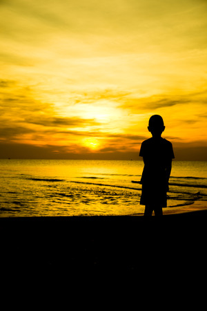 lonely boy: lonely boy on the beach Silhouette Stock Photo