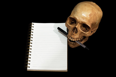 Skull note taking still life black background, Clipping path