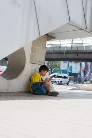 union familiar: BANGKOK, Tailandia FEBRERO 7,2016: El niño no identificado en juegos de prensa está viviendo debajo de un puente turistas vienen a visitar el arte de Bangkok y el centro de la cultura en Pathumwan unión, Bangkok arte y centro cultural es el primer centro de arte moderno en Tailandia, febrero 7 2 Editorial