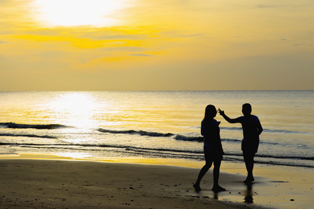 portly: Two women greet each other on the beach at sunset.Selective focus at woman