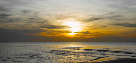 Sun sets over horizon of ocean. Sky, water and shore in the evening painted. Stock fotó