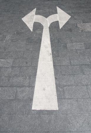White arrow on asphalt surface. Urban background.