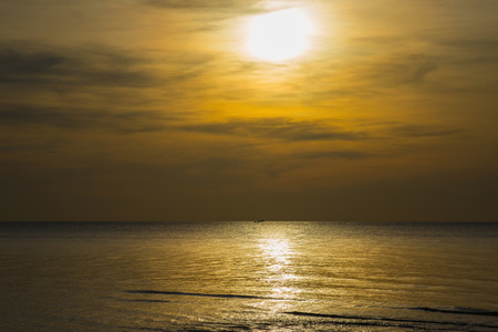 Sun sets over horizon of ocean. Sky, water and shore in the evening painted in orange, gold color.