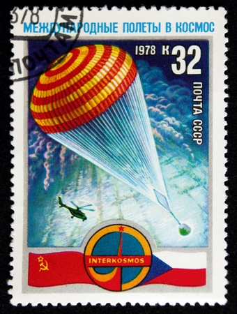 a stamp printed in the ussr shows parachute with spacecraft capsule,circa 1978