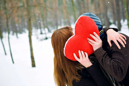 Couple with red heart kissing