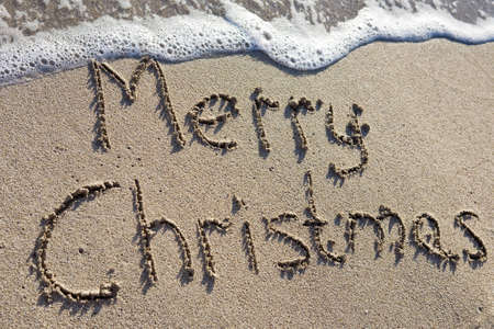 Merry Christmas written on the sand photo