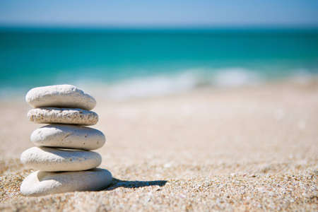 Stack of white stones on tropical beach photo