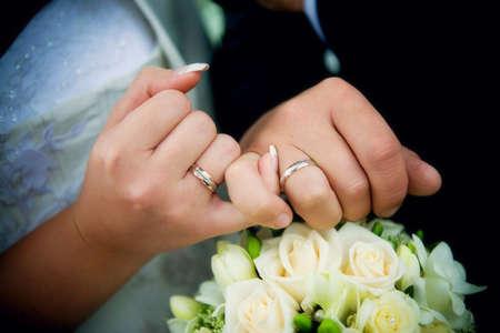 Mains avec anneaux et bouquet de mariage
