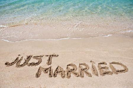 Just married geschreven in het zand
