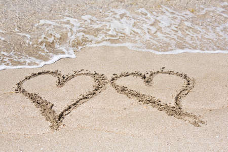 Two hearts drawn in the sand photo