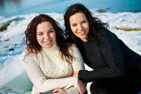Girls twins near river in winter
