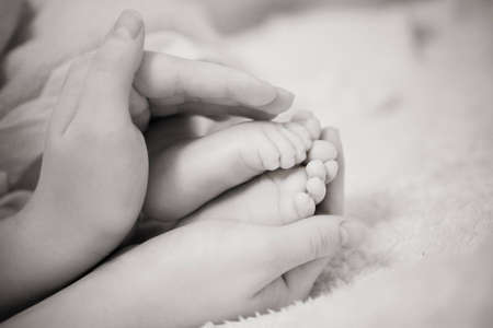Babys feet in his mothers hands photo