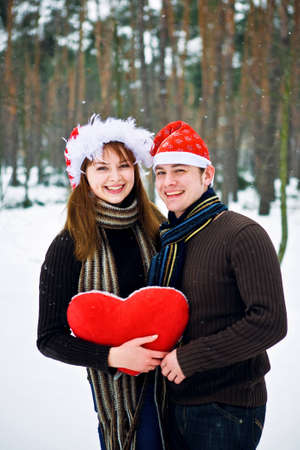 Couple in love with a red heart and Christmas Hats photo