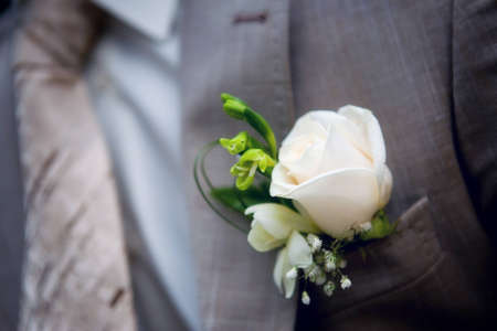 Boutonniere on a mans jacket, white rose