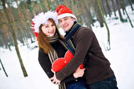 Couple in love with a red heart and Christmas Hats