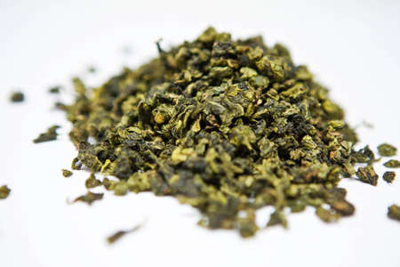 Green tea leaves on a white background