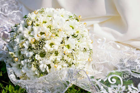 Bridal bouquet on white dress Stock Photo