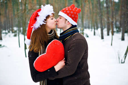 Couple in love with a red heart and Christmas Hats Stock Photo - 10367912