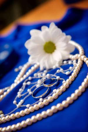Wedding rings and flower on a blue dress Standard-Bild