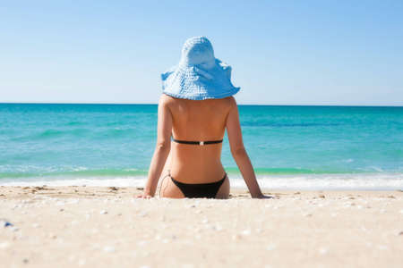The girl on the beach wearing a hat
