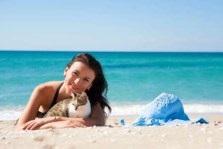 Girl on the beach with a kitten and wearing a hat