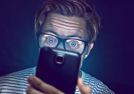 Jonge man verslaafd met zijn smartphone