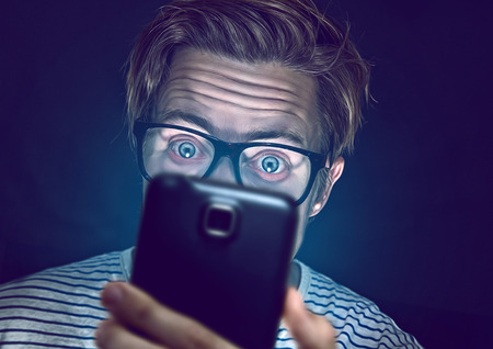 smartphone addiction:   Young man addicted with his smartphone Stock Photo