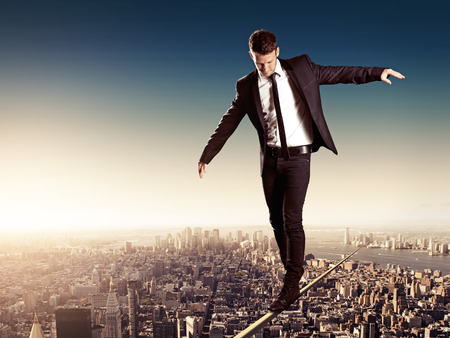 Business man walking on high wire in big city
