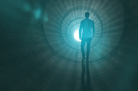 near death: Man walking to the light at the end of the tunnel