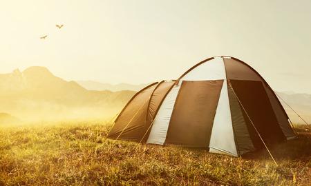夕暮れ時の山でテント