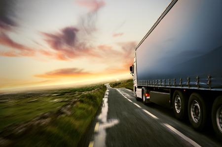 Camión en una carretera nacional al atardecer Foto de archivo - 75280573