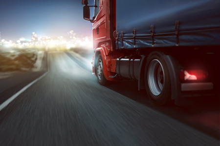 Truck drives on a country road with bokeh lights in the distance