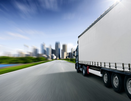 Truck driving towards big city Stock Photo