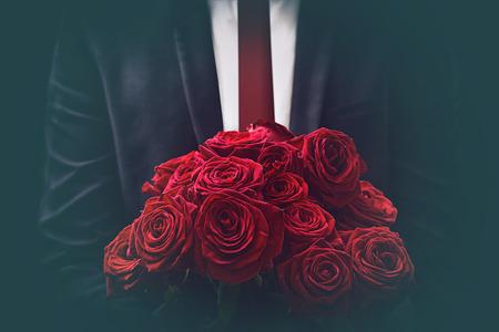uomo rosso: L'uomo offre un bouquet di rose Archivio Fotografico