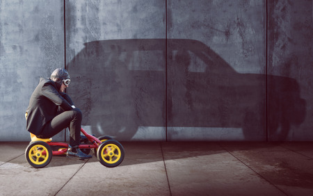 strive for: Ambitous Businessman on a pedal car Stock Photo